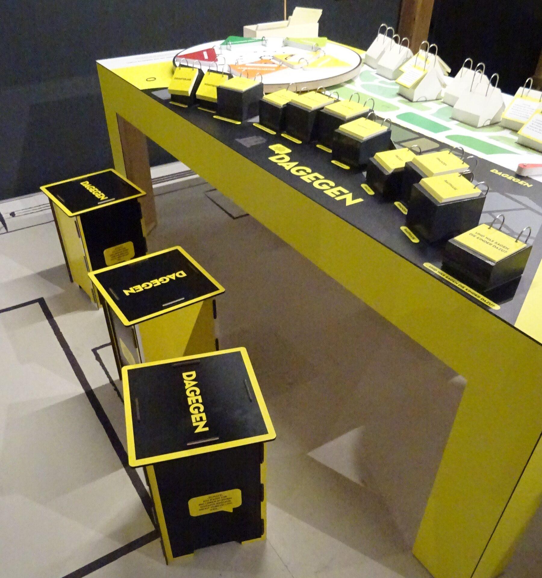Gelber Tisch, viele Spielkarten und drei Hocker